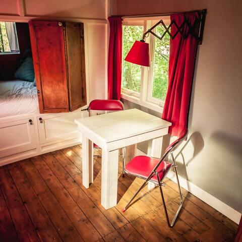 Vier klapstoeltjes, een zitstoel en een tafeltje aanwezig