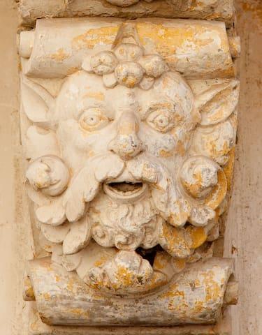 La zona: Maschera barocca in pietra leccese ubicata sulla facciata di una chiesa