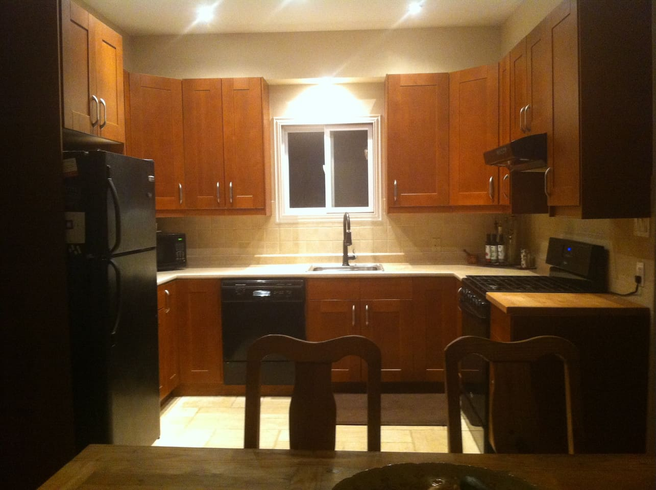 Large kitchen fully outfitted with all appliances, including food processor, microwave, and dishwasher
