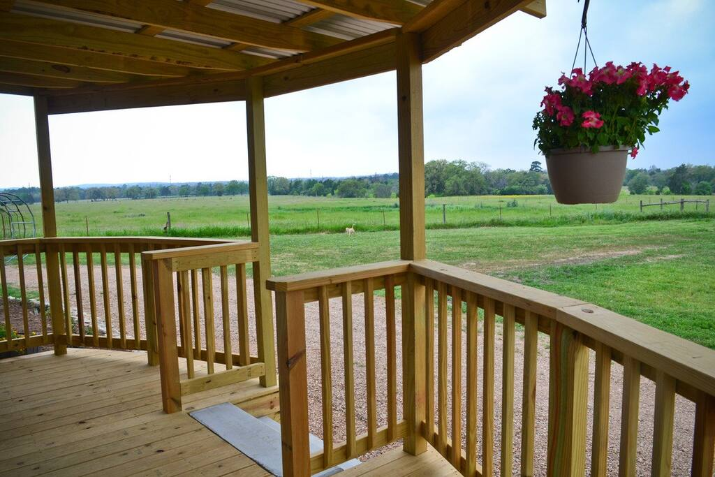 Views to hundreds of acres of a working cattle ranch from a covered deck. Features gas grill and patio seats.