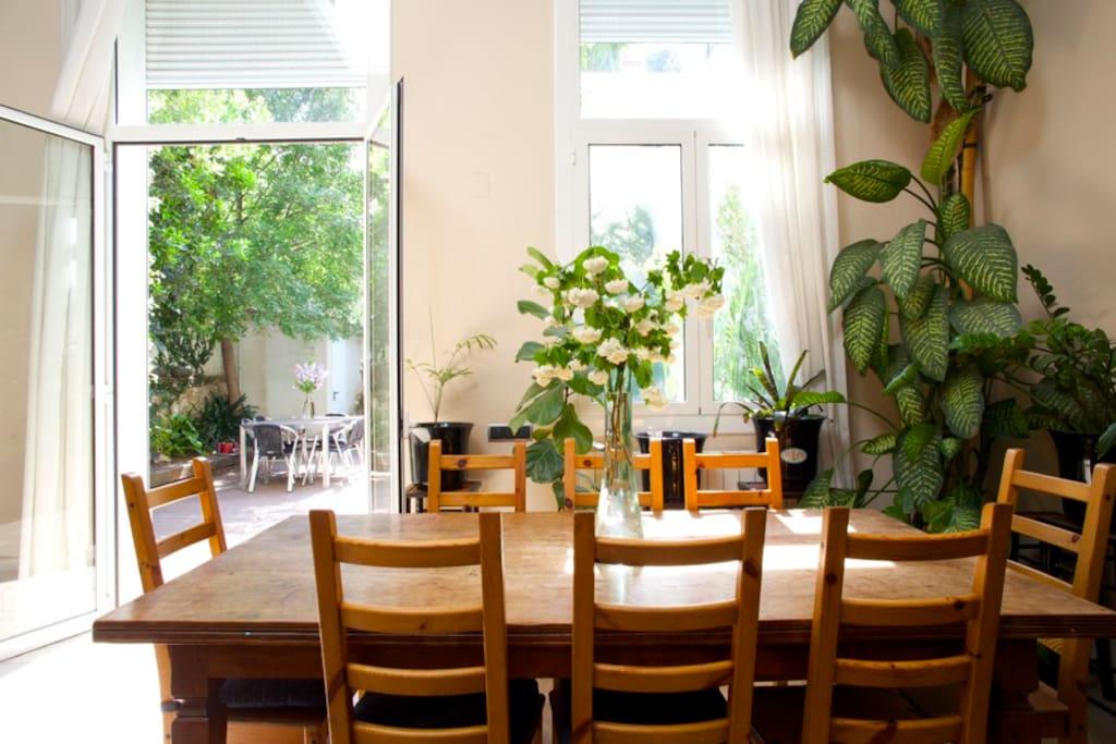 Mesa comedor para 8 personas abierta al jardín.