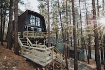 Treehouse Vibes rests on a hill, making you feel like you're in a tree house overlooking the quiet neighborhood. The trees that surround the cabin provide natural privacy. Please note the neighboring structure to the right.