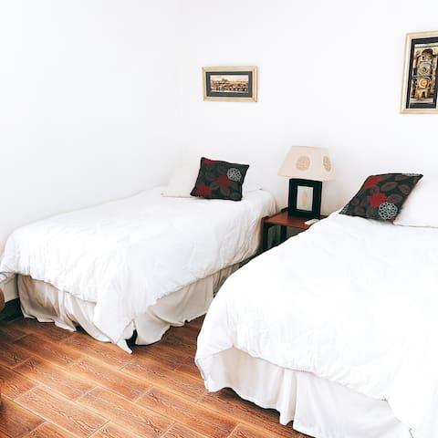 Tercera habitación con dos camas single y vista a las montañas.