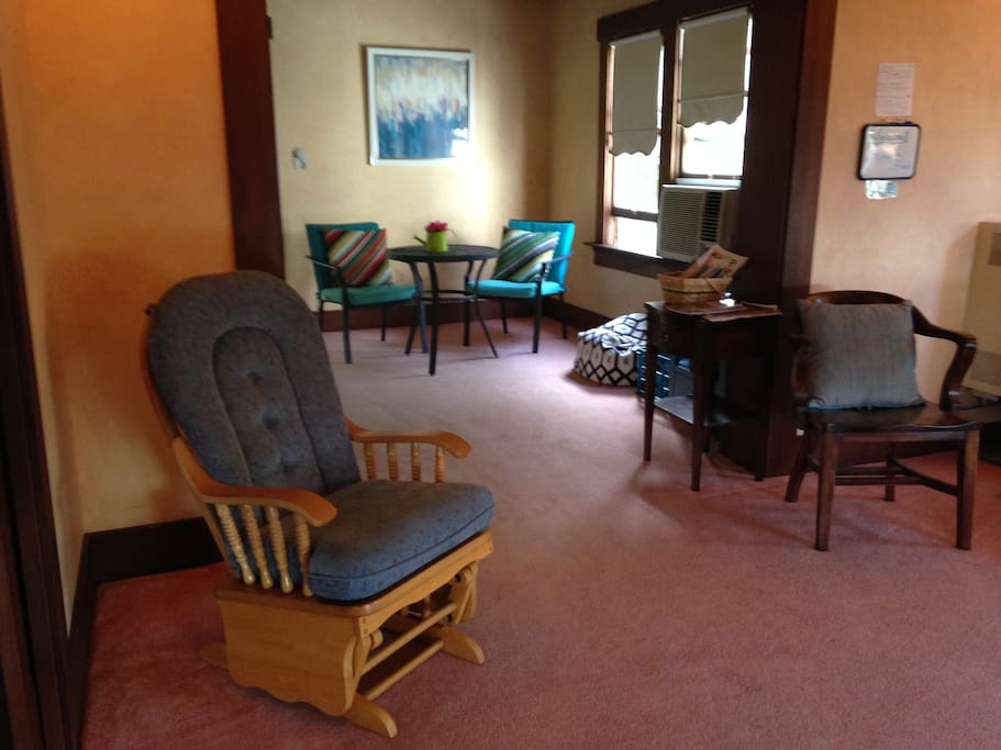 Padded rocker and chair in front parlor with WIFI table in back.