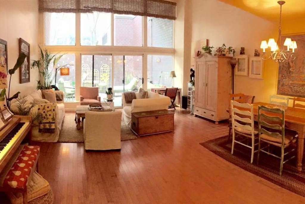 Spacious living room with high ceilings, floor to ceiling windows and a patio.