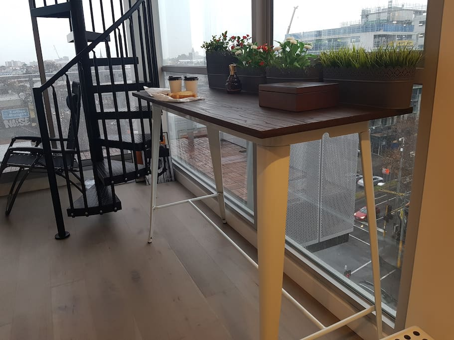 a spiral staircase connects the top from the bottom. a high bench top for quick meals before your day of city adventures
