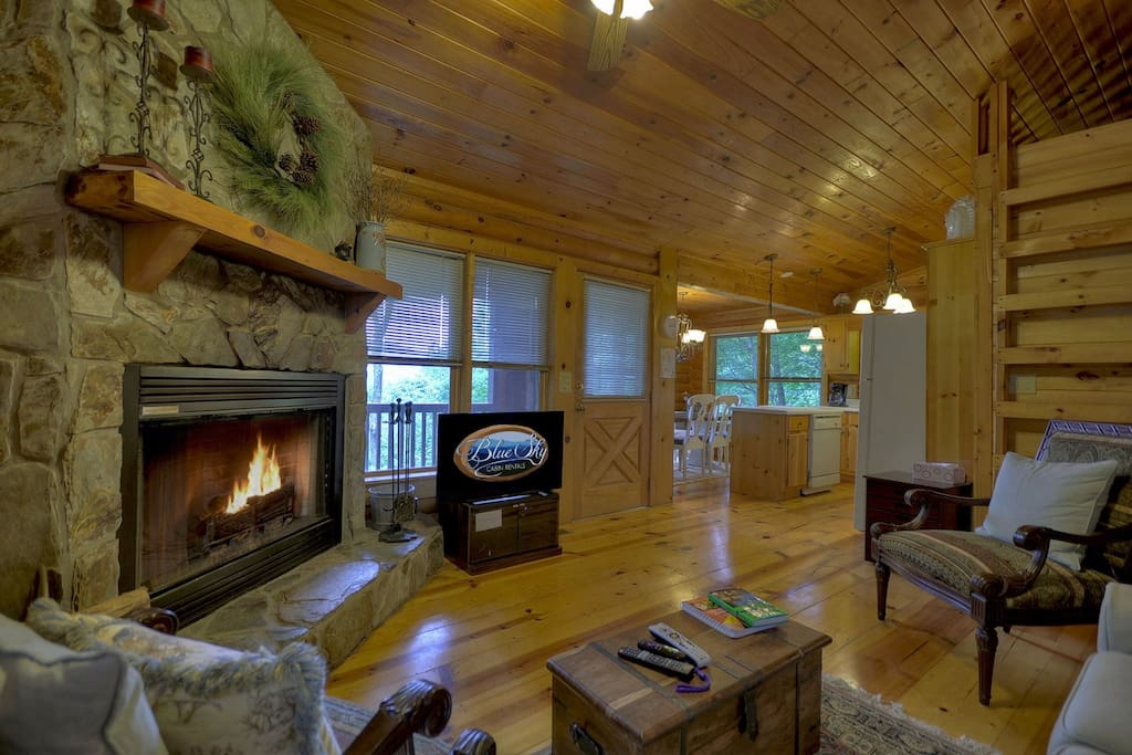 beautiful great room with flat screen TV and stone, wood burning fireplace