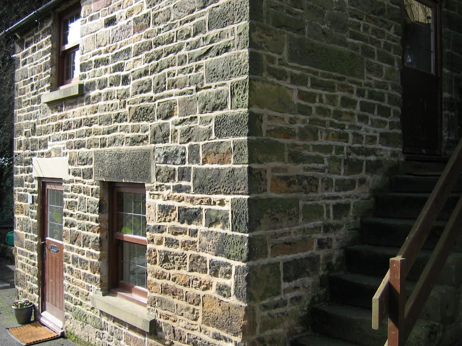 External stone steps lead to door into living room - which is upstairs.