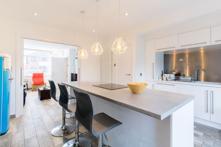 Modern kitchen with island and open plan or french doors leading into living room