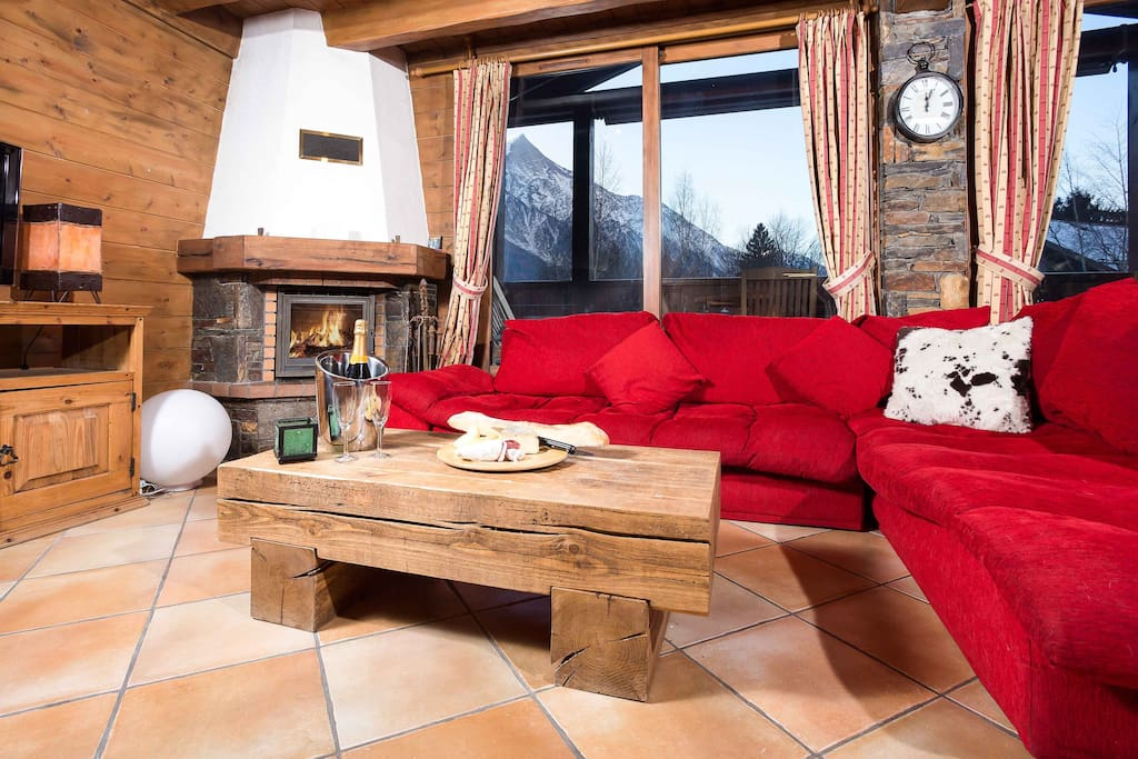 Chalet style lounge with log fireplace, leading onto balcony