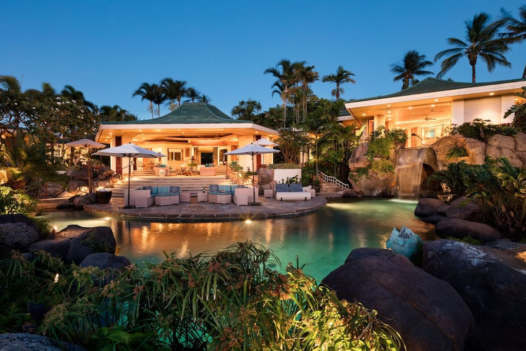 Twilight view of estate home with pool, pool deck, lanai, great room, and master suite (on right).