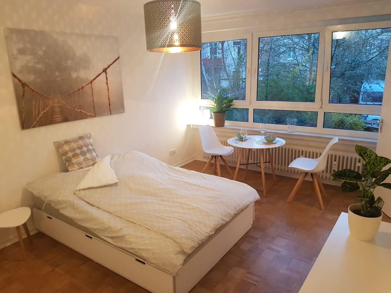 Großer Wohn/Schlaf- und Essbereich mit Blick ins Grüne.  (140x200 Bett, Kleiderschrank und Essplatz)  Spacious living/sleeping and dining room with view into greenery.  (140x200 bed, closet and dining table)