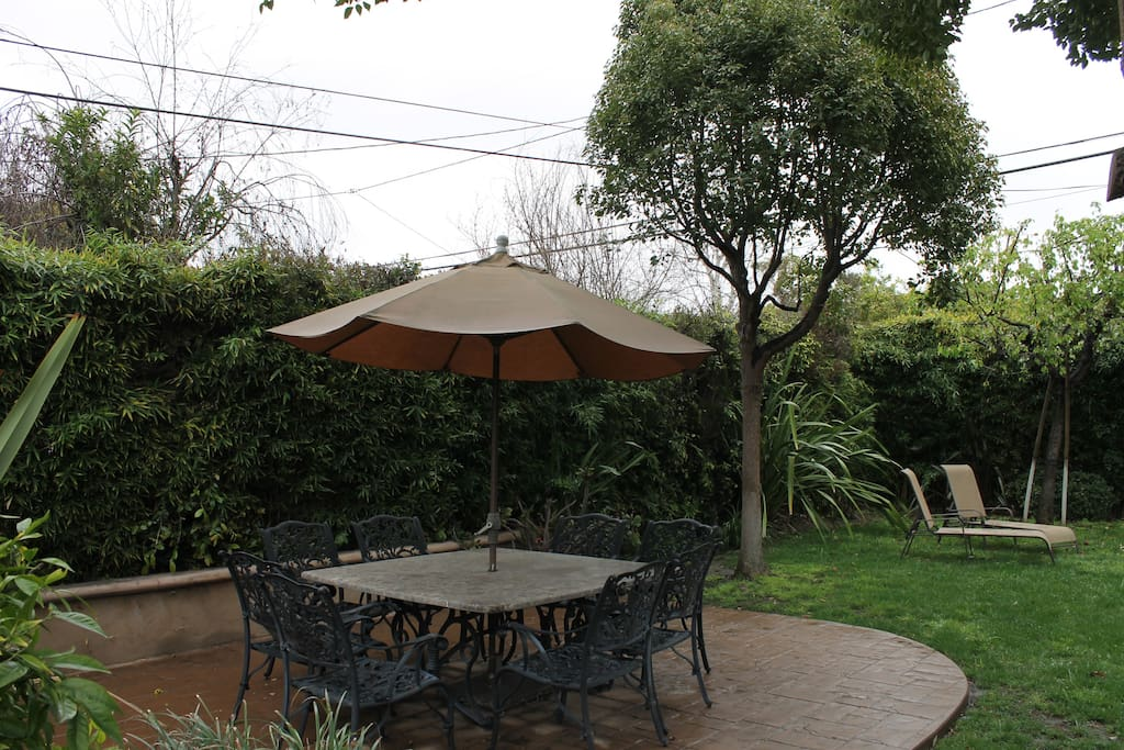 a big green backyard with outdoor dining set  with 8 chairs