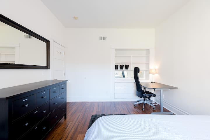 Private master bedroom with queen-sized bed, desk, chair, mirror, and large window.