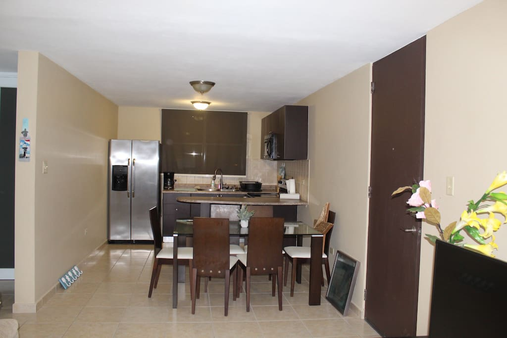 Stainless steel refrigerator, table seating for six, microwave, electric stovetop, stocked with cutlery, pots, & pans