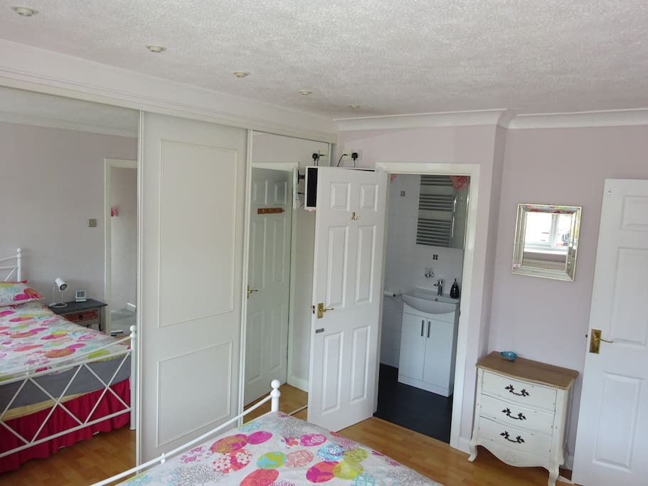 There is a large fitted wardrobe and a TV in the room.