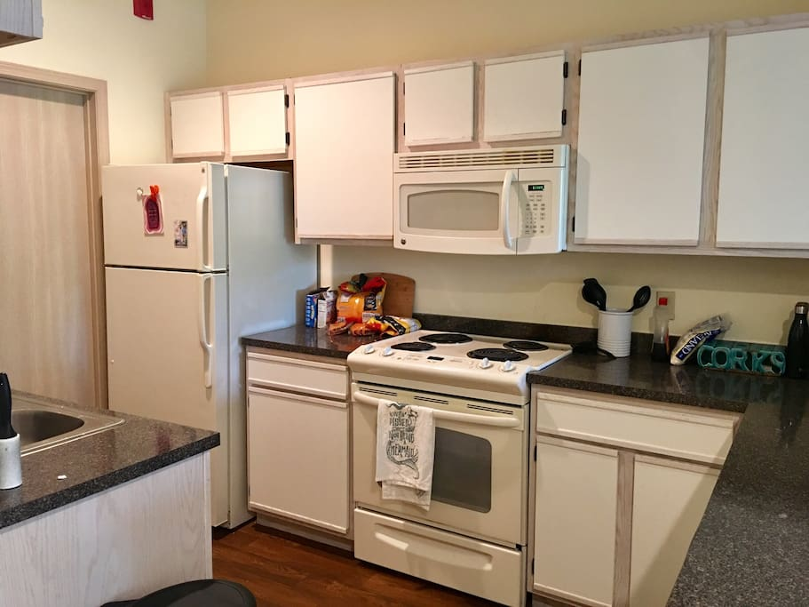Kitchen area. Full refrigerator, oven, stove, microwave, dishwasher, coffee maker, cooking supplies and utensils.