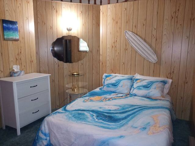 2nd Bedroom with Queen size bed Located next to the room with 2 single beds. This bedroom has a closet with extra sheets, blankets, an ironing board and a small dressser.