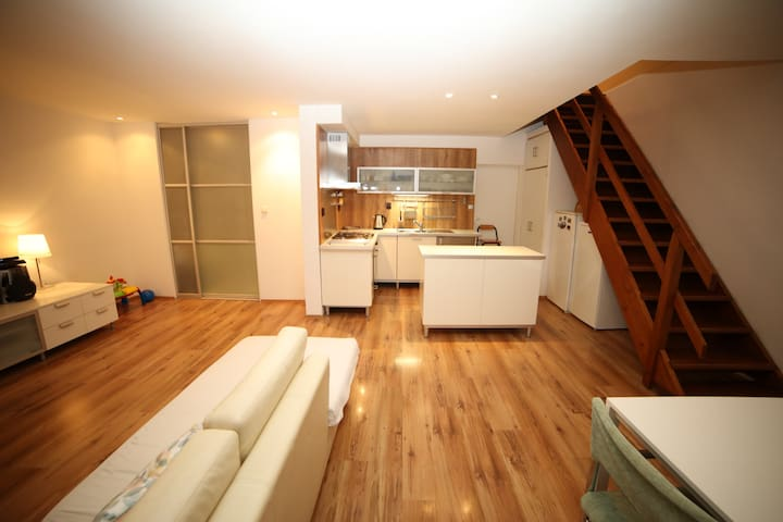 Open plan kitchen/dining/living room, with wooden staircase leading up to the top floor's rooftop section containing two adjacent rooms with ensuite bathroom.