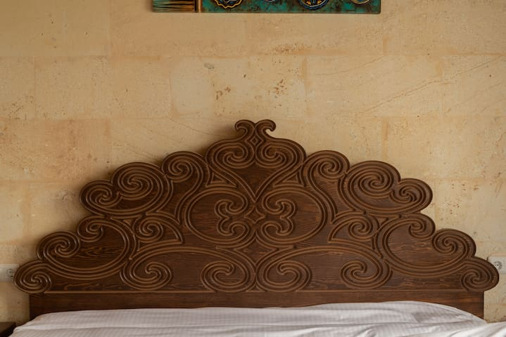 Detail of the hand carved wooden bed headboard