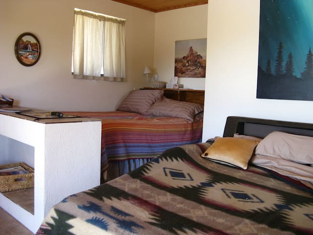 Bunkhouse interior with sofa bed and full sized bed.