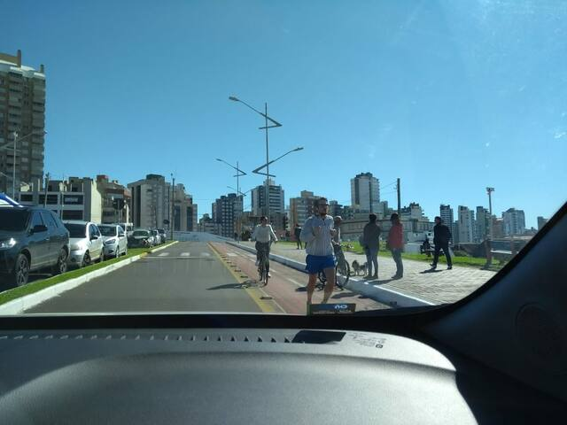 Foto da orla, em Torres/RS. Calçadão, ciclovia, estacionamento na orla.