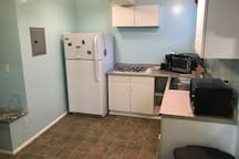 Fridge, coffee maker,  stovetop, countertop convection oven, sink, microwave, pots