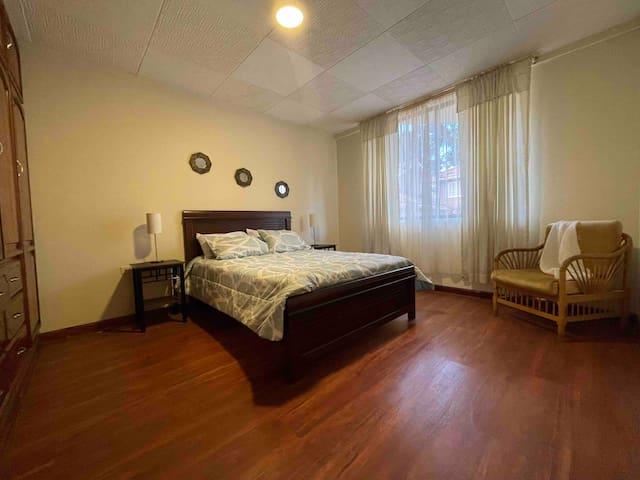 Este dormitorio tiene una cama matrimonial (queen-sized bed), 2 mesitas de noche, un sillón y un clóset grande con espejo.