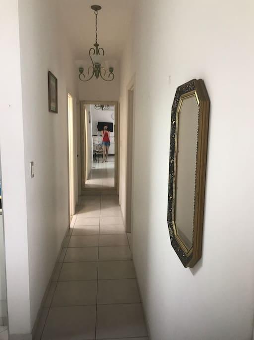 Corredor para a entrada dos quartos com espelhos decorativos.