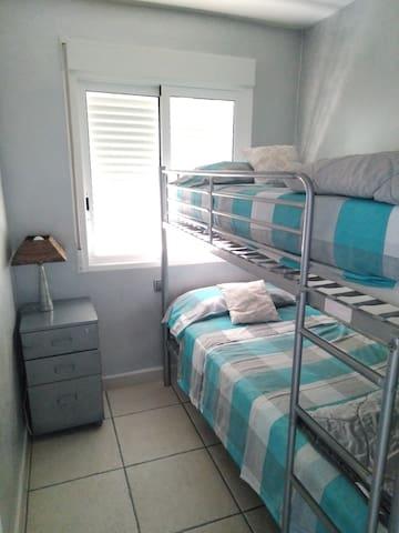 Habitación secundario con dos literas individuales y una mesita de noche