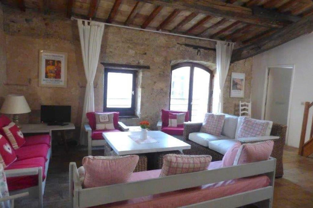 Wohnzimmer mit grossen Fenstern und viel Charme durch sichtbares  Mauerwerk