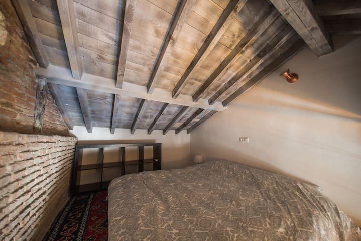 Mezzanine bedroom under the wooden ceiling