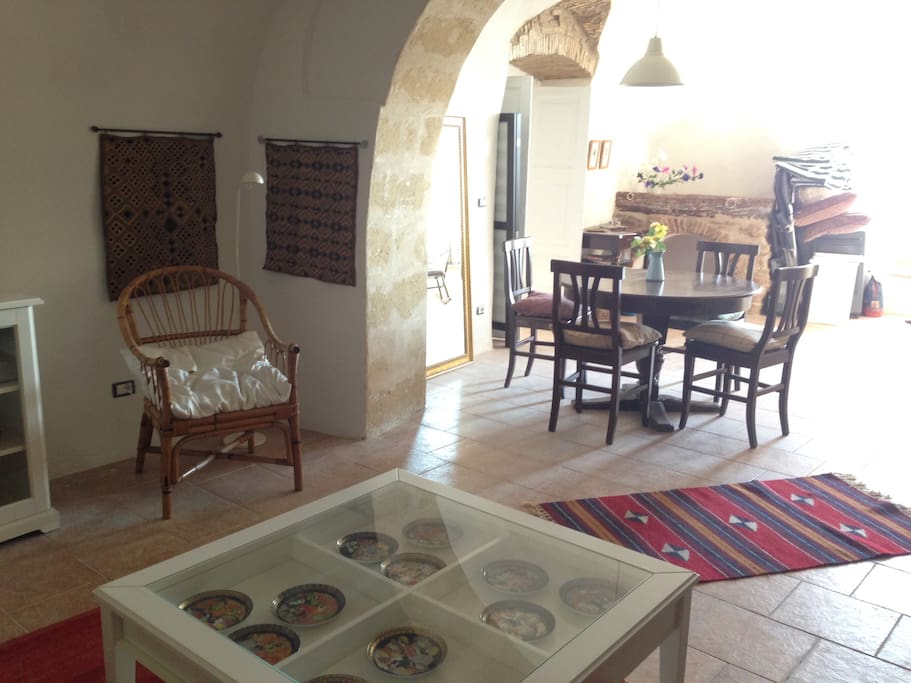 Spacious living area with tufo walls and arches.