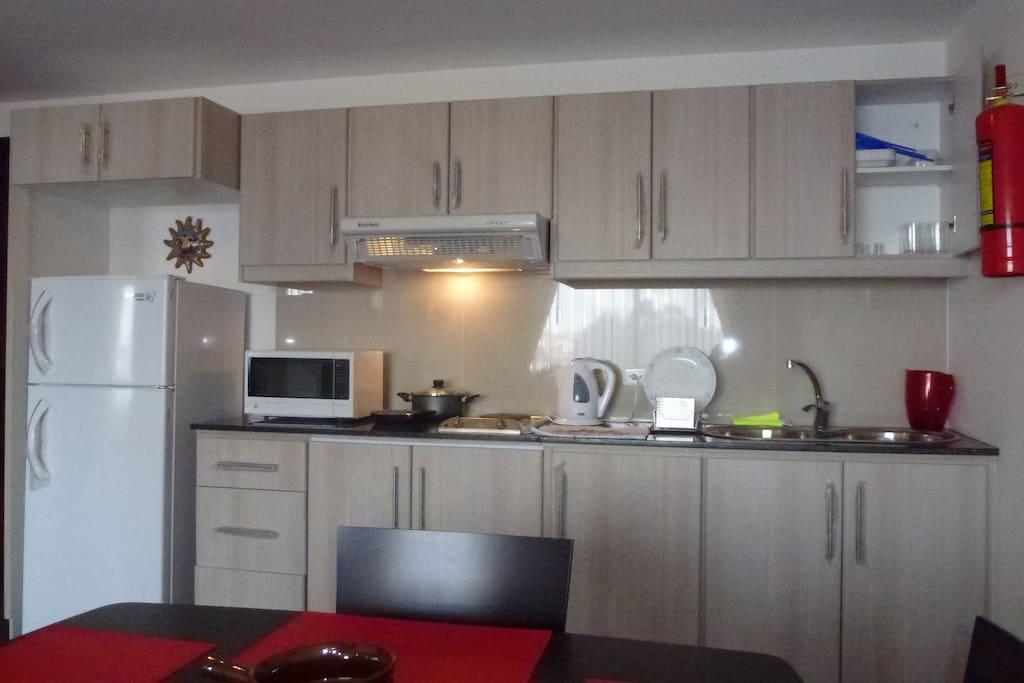 Cocina equipada: Refrigeradora, microondas, ollas, estufa eléctrica, licuadora, cafetera, vajilla, cubiertos, vasos, etc.