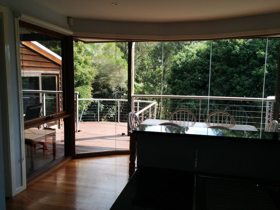 Taken from the middle of the kitchen, looking at the sunny dining table and beautiful northern bushy outlook and views, with lots of deck space.