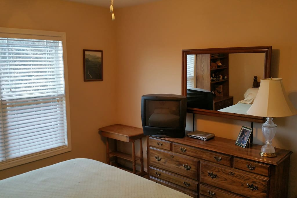 Comfortable Guest room with TV and lots of sun.