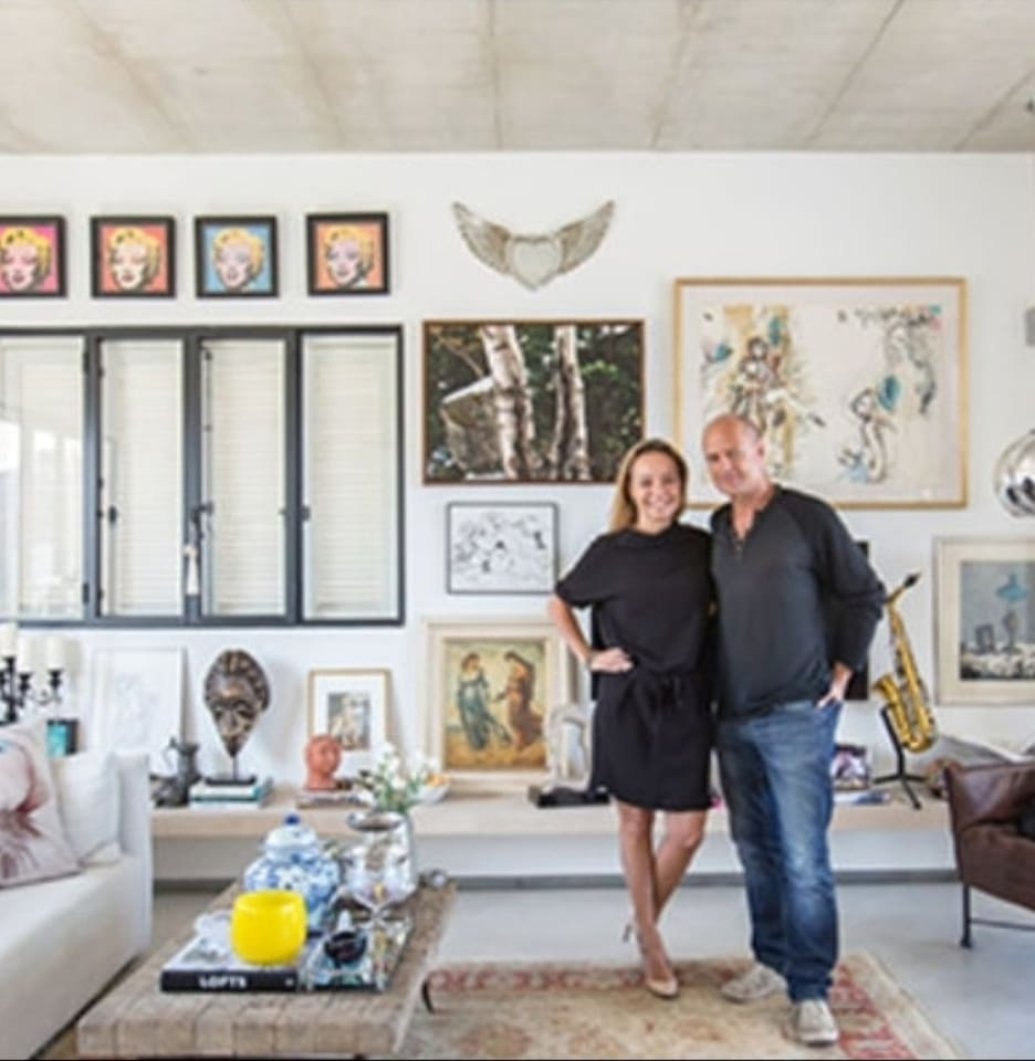 Photographed by Hila Ido showing the owners at the backgrond of the living room.