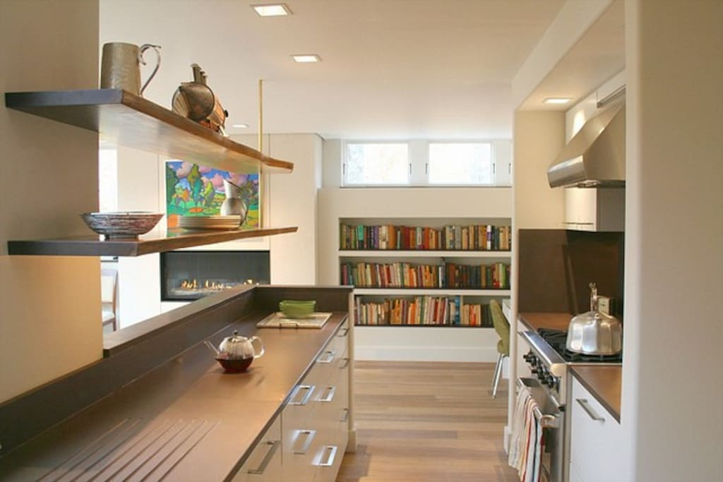 Galley kitchen with chocolate slate countertops,  under-counter refrigerator, Wolf stove, and live-edge walnut shelving.