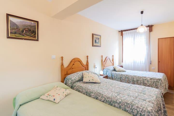 Habitación con cuatro camas individuales y baño completo.
