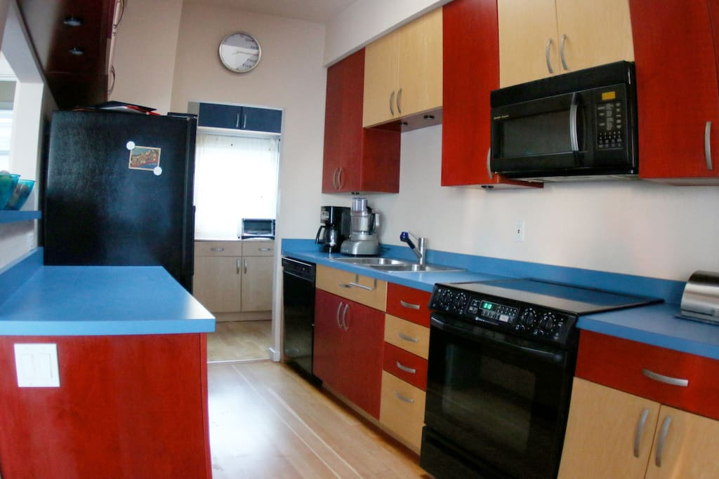 European kitchen with blender, coffee maker, microwave, stove, pots, pans, spices, and everything what belongs in a functional kitchen
