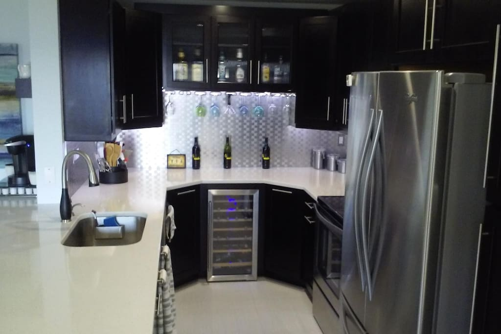 Kitchen that includes a wine fridge, dishwasher, microwave, stove, fridge and garbage disposal