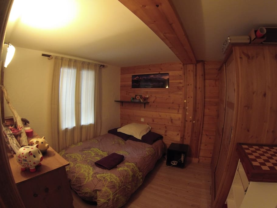 upstairs bedroom off living area, with double bed and wardrobe