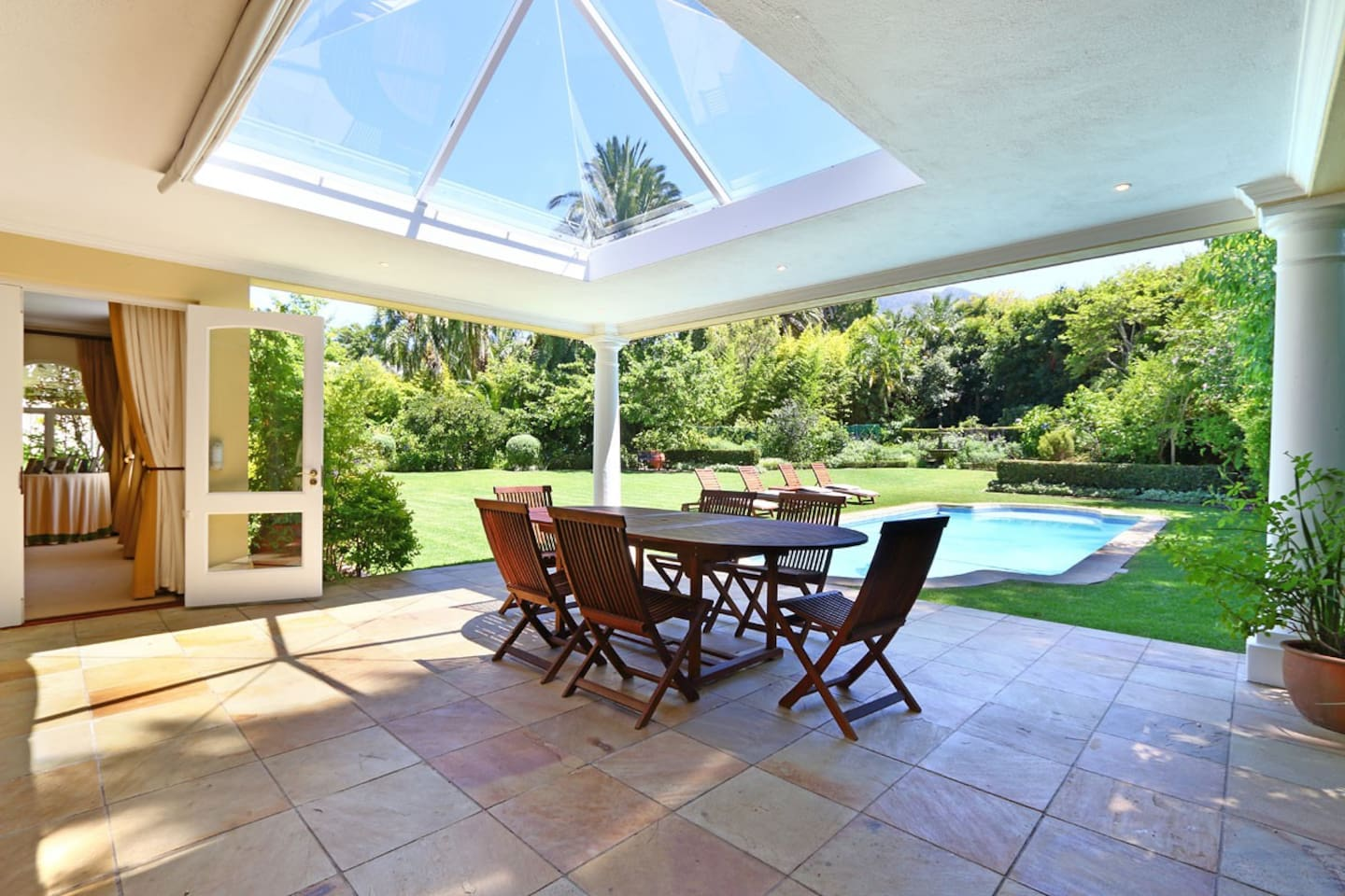 Outdoor covered patio leading onto pool and private garden