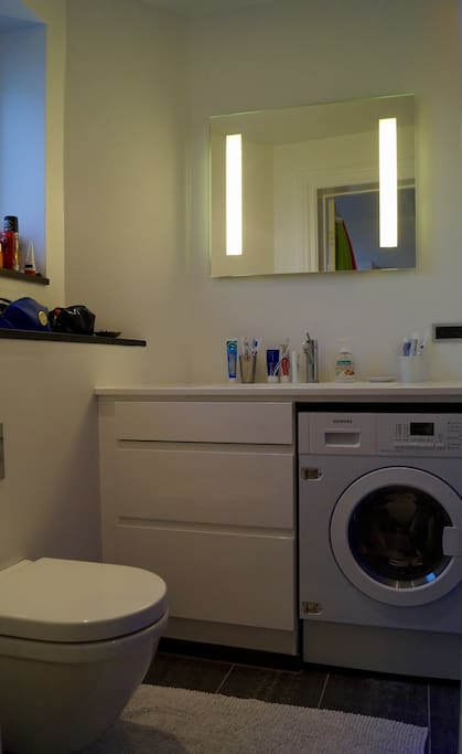 New and modern bathroom with a washing machine and dryer