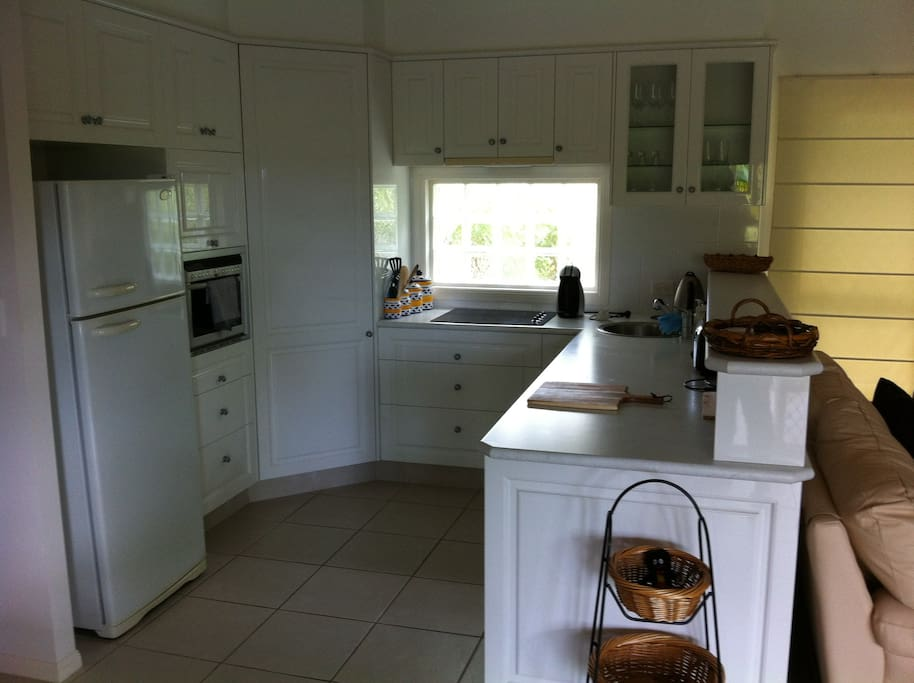 Lovely self contained white kitchen with fridge/freezer, dishwasher and walk in pantry. Oven hot plates and all appliances. Kitchen is well stocked with all your essential cooking requirements.