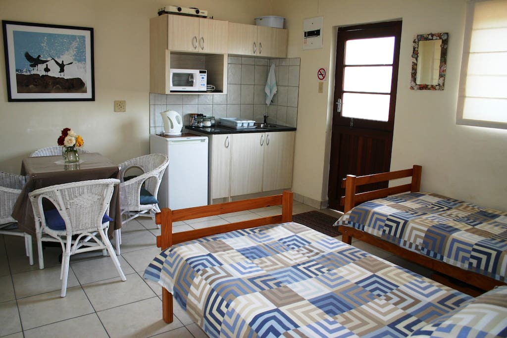 Open plan living room with two single beds and kitchenette with private entrance.