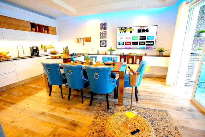 """SUITE54 - Living room with 65"""" smart TV, designer double sofabed and a fully equipped luxury Italian designer kitchen. All rooms have the Amazon echo music system & the newest Apple TV to deliver best entertainment experiences."""