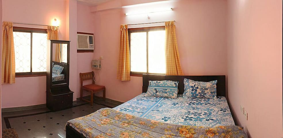 Master bedroom with attached European WC. Chairs, dressing table and wardrobe are provided.