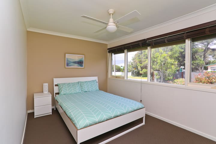 Bedroom 2 with queen bed, built in wardrobe and ceiling fan.