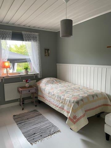 Sovrum med en enkelsäng.  Ett mysigt sovrum som ligger på övervåningen intill master bed room.  I rummet finns en garderob och en klädstång för förvaring.  Mörkläggningsgardin.